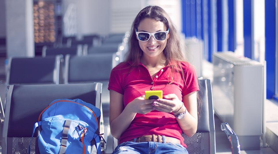 Viajante usando celular em aeroporto