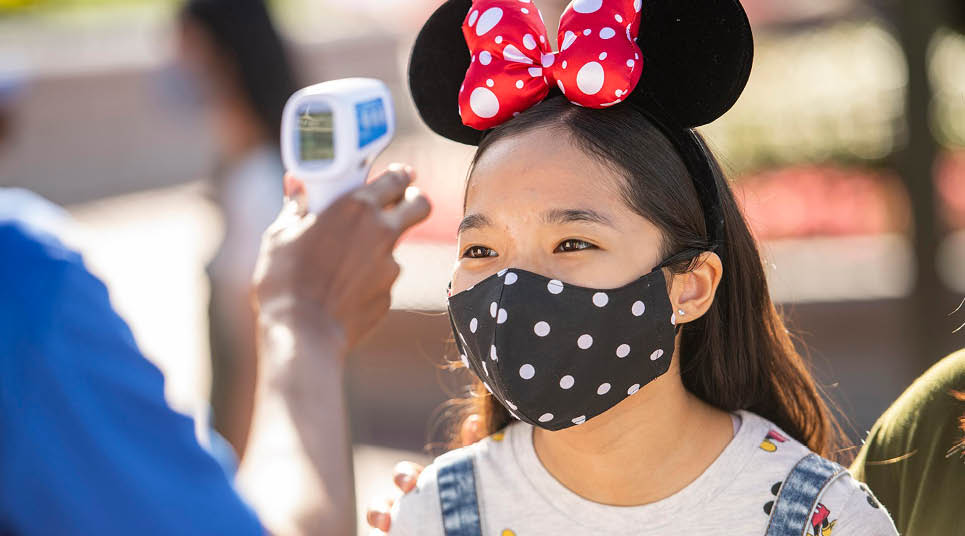 Visitante medindo temperatura nos parques da Disney