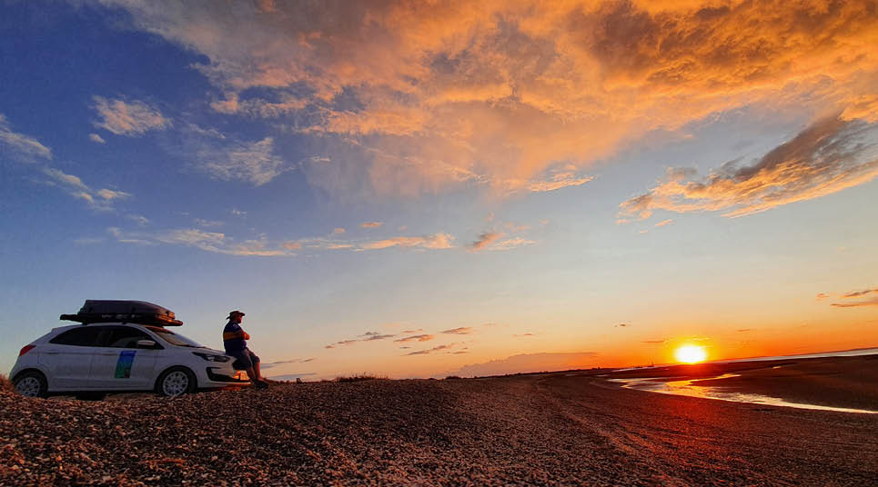 Gustavo admira o pôr do sol junto ao seu Ford Ka