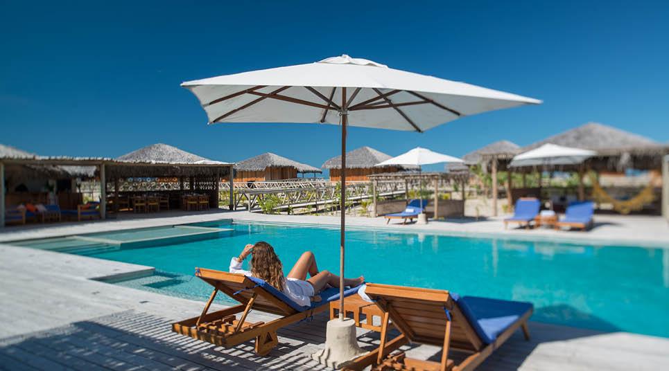 Hóspede relaxa em frente à piscina do hotel